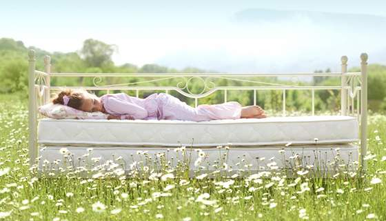 A child sleeps on a bed outdoors in a green field with white flowers and blue skies.
